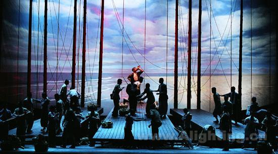 """在装置选择上舞美也会越来越多的考虑灯光的影响,如三块船板模拟的三条战船,在灯光营造的氛围当中,每条船都独立布光,单独控制,根据剧情需要随时调控每块船板的光色氛围,对于这场戏的辅助作用是显而易见的。运用高色温的电脑灯具通过对现实光色的加强和渲染,在舞台上均匀的渲染出高于写实之外的光的空间,从而让实景和演员(包括演员的服装)完全融合在光色氛围中间,让观众在紧张的气氛当中不知不觉地融入到戏中,对整体的舞台表演发出由衷的赞叹。 在""""海战""""一场戏中,通过灯光战争气氛的渲染和光束造型的运"""