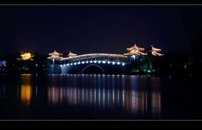 徐州小南湖风景区,四面环水,景色秀丽宜人,夜幕下的拱桥,色彩斑斓